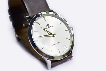 silver-colored analog watch with brown leather strap on top of white surface