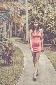 woman wearing pink crew-neck sleeveless dress walking on concrete pathway