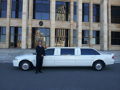 man standing beside white limousine