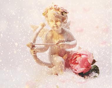 cherub holding bow beside flower