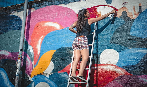 woman on ladder painting on wall