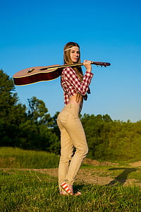 woman carrying brown and white acoustic guitar on green grass during daytime