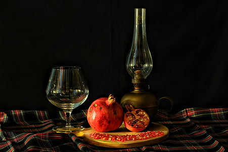 pomegranate between wine glass and oil lamp on table