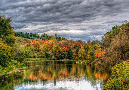 lake surrounded by trees under heavy clouds