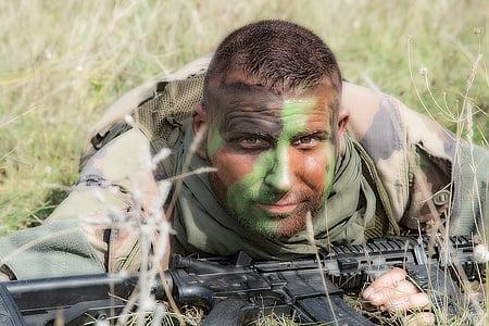 man wearing army uniform holding rifle