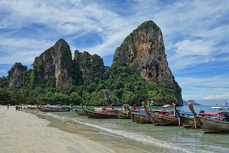 boats docked at beach near rock mountain