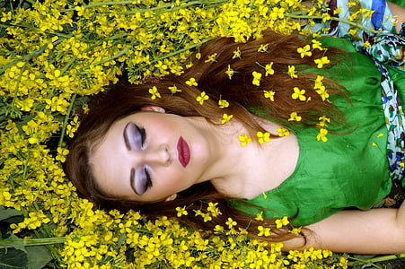 woman in green sleeveless top laying on yellow flowers