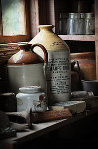 several stoneware jugs on wooden table near rack