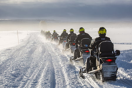 crowded people riding vehicle on snowfield at daytime