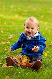 toddler wearing blue zip-up jacket smiling