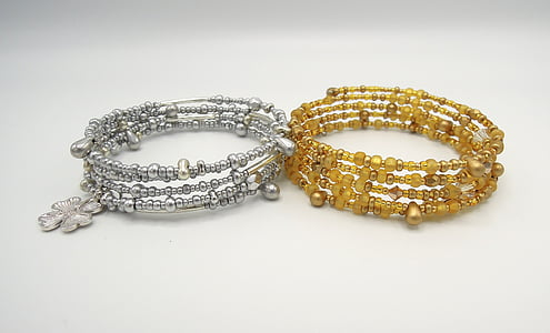 two beaded gray and beige bracelets on white surface