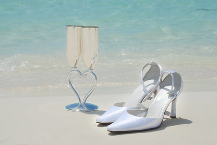 pair of white pointed-toe pumps near wine glasses in seashore