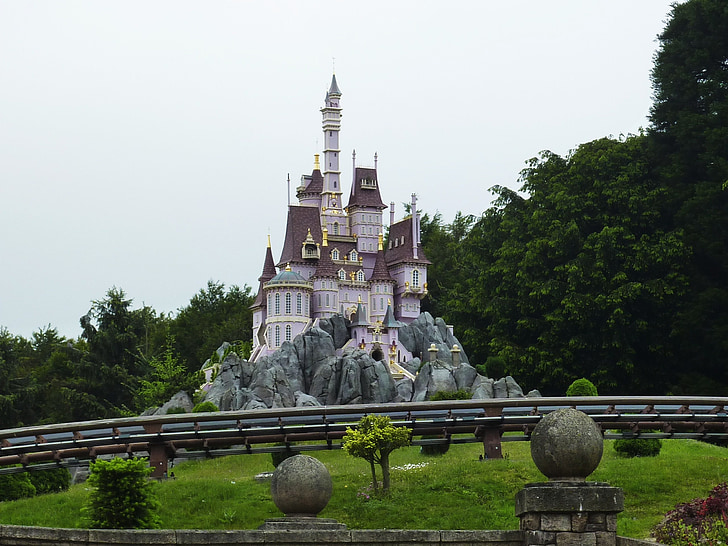 white and pink castle beside trees