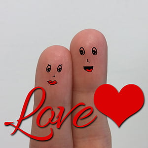 person's finger with love text overlay