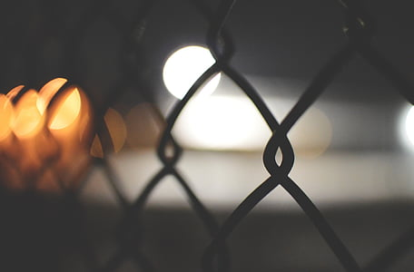 white and yellow camera lights effects on cyclone fence