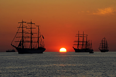 three galleon on body of water during sunset