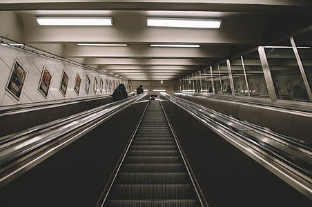 person in black jacket riding on escalator