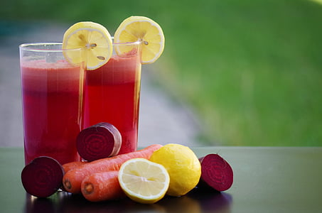 selective focus photography of two glass of juices with lemon and carrots