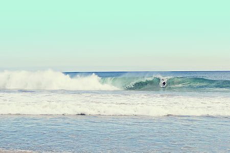 person surfing on waves during daytime