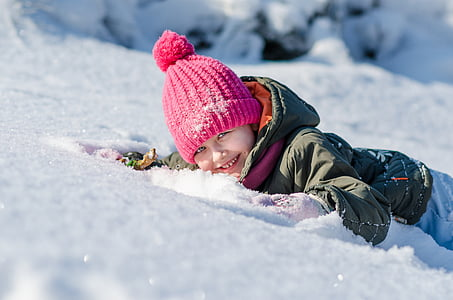 toddler in gray jacket lying on snow field
