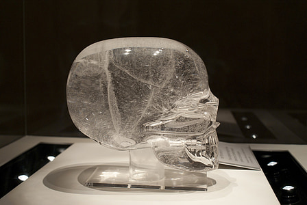 clear glass skull figurine on table