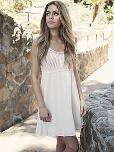woman in white scoop-neck sleeveless dress standing near wall