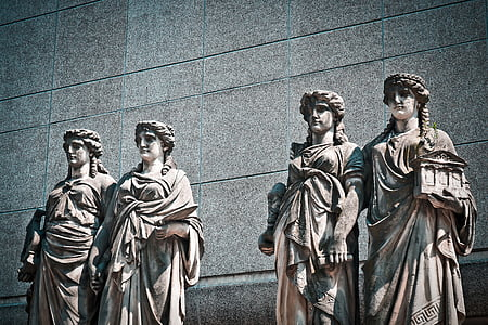 four white statues standing near gray wall