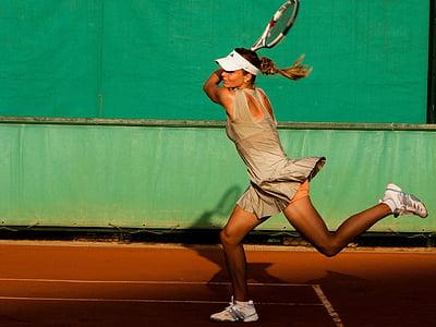 woman in grey tennis uniform playing tennis