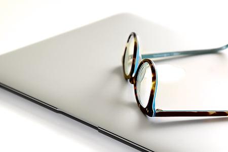 round black framed eyeglasses on white wooden surface