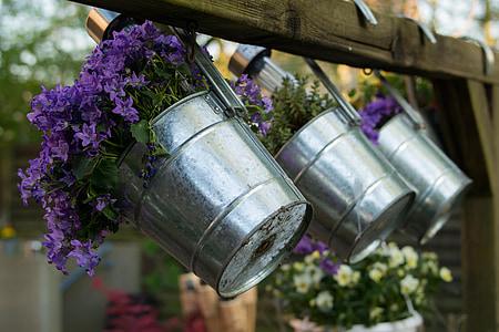 purple flowers in silver buckets