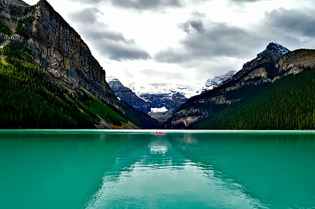 teal calm body of water in distance green mountain under white cloudy sky during daytime