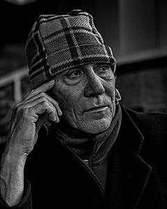 man thinking outside house