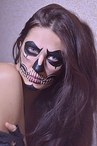 photo of woman putting skull makeup