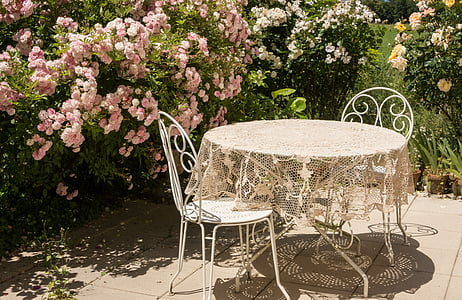 beige floral table cover on round white patio table beside two chairs