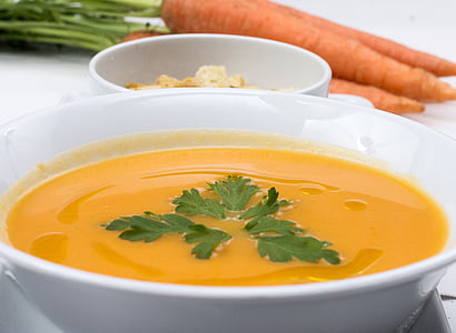 soup in white ceramic bowl beside carrots