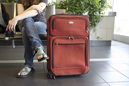 woman sitting beside red travel luggage