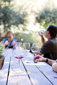 three wine glasses on gray wooden picnic table