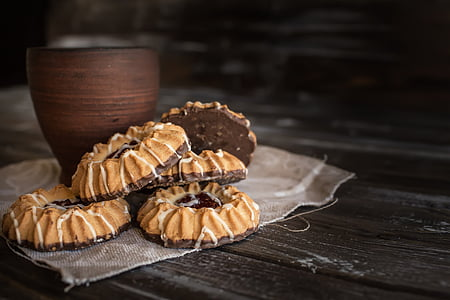 five cookies with brown wooden cup