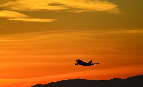 airplane taking off during sunset