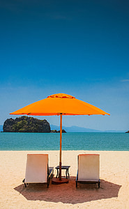 two beach loungers under orange umbrella at seashore under blue calm sky