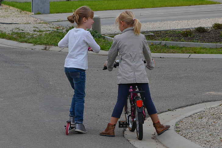 girl riding bicycle and kick scooter on road