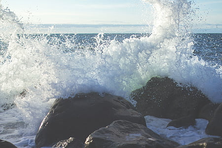 splash of wave on black rocks at daytime