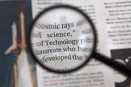 Technology word in magnifying glass
