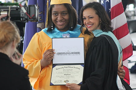 woman standing next to another woman holding diploma