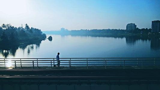 man standing on the bridge facing body of water