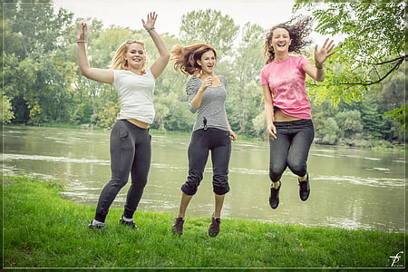 three woman jumping beside body of water