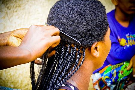 person braiding woman's hair