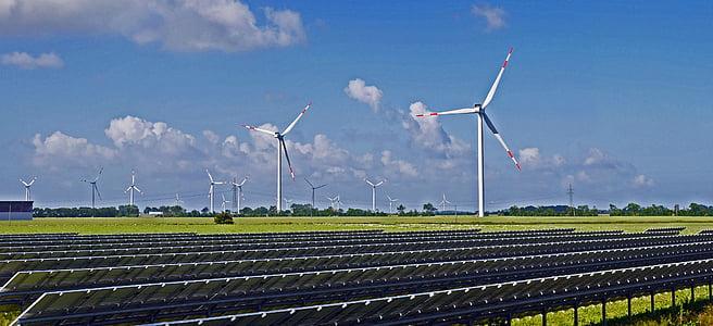 photo of wind turbine on field near solar panel