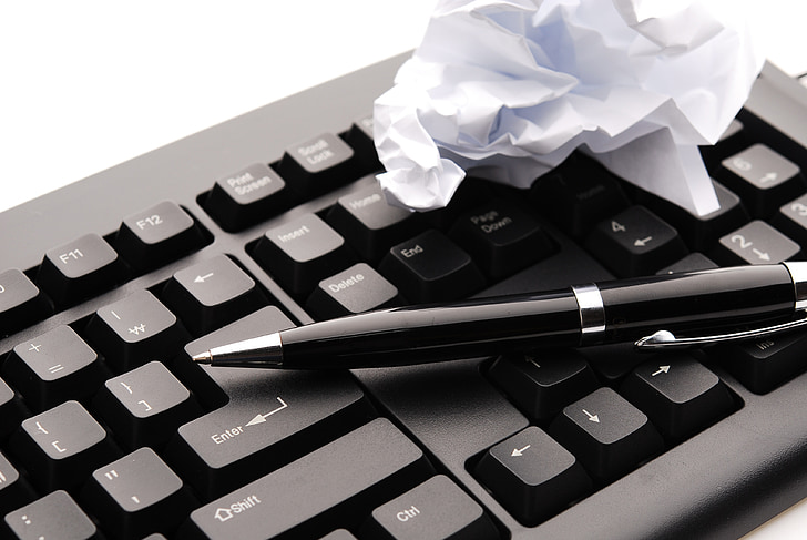 black retractable pen on computer keyboard