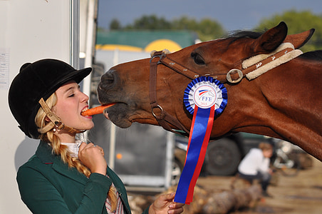 woman biting carrot with horse